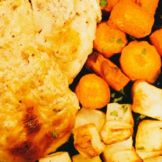 cheesy baked chicken served with a side of carrots and potatoes