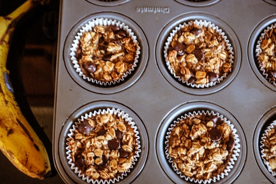 banana chocolate chip muffins in a tin with banana on side