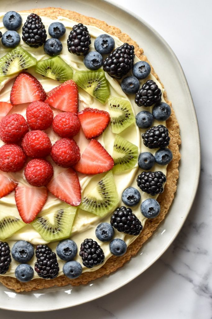 close up of fruit pizza with strawberries, kiwi, blackberries and blueberries