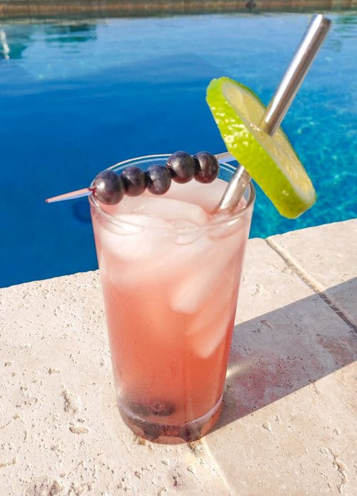 blueberry vodka spritzer in a glass near a pool