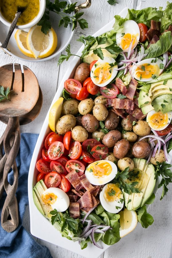 potato cobb salad on a plate with lemons on side