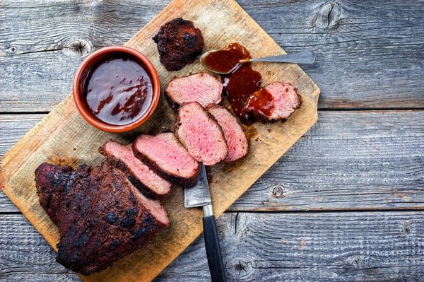 slided tri tips on a cutting board with bbq sauce