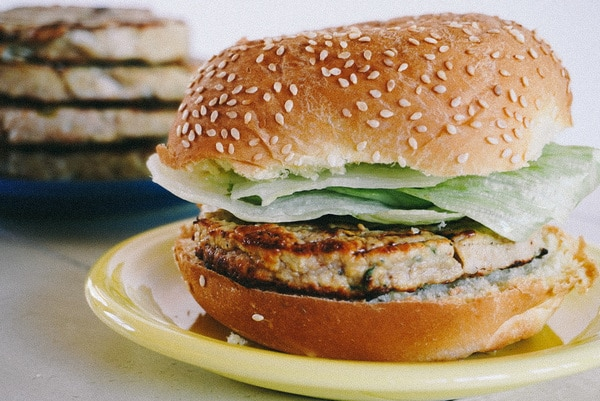 close up of a juicy turkey burger with lettuce and bun on a yellow plate
