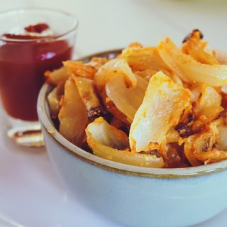 close up of onion strings in a blue bowl with ketchup