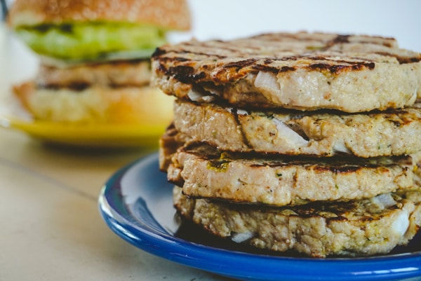 stack of 4 cooked juicy turkey burgers on a blue plate