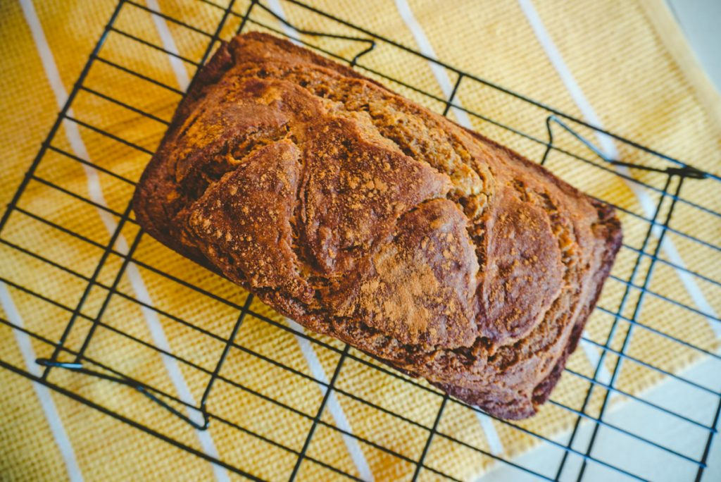banana bread on a wire rack over a yellow towel