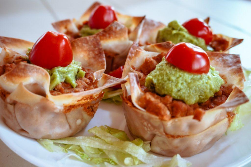 close up of chicken burrito cupcakes with tomato and guacamole
