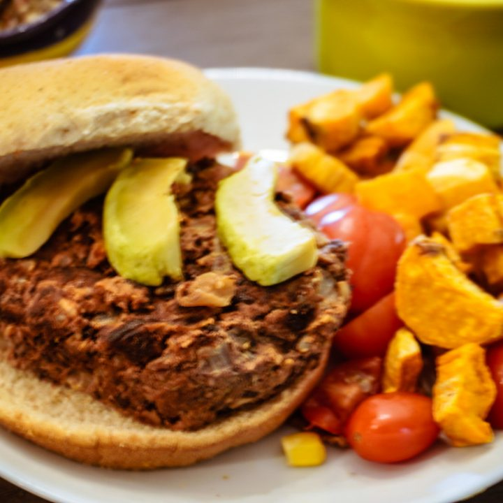 burger on a plate with avocado and tomatoes