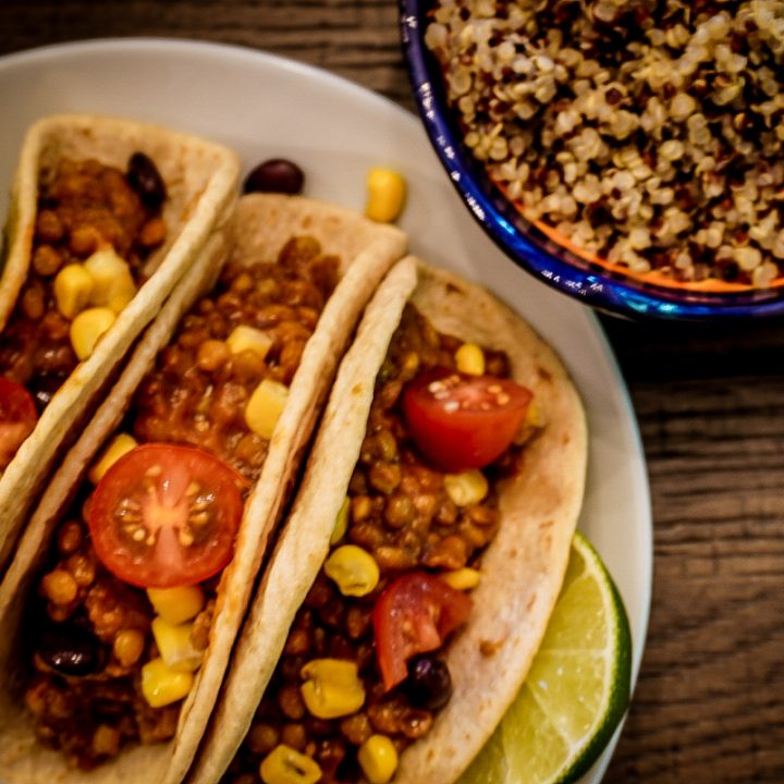 street tacos on a white plate with a side of quinoa