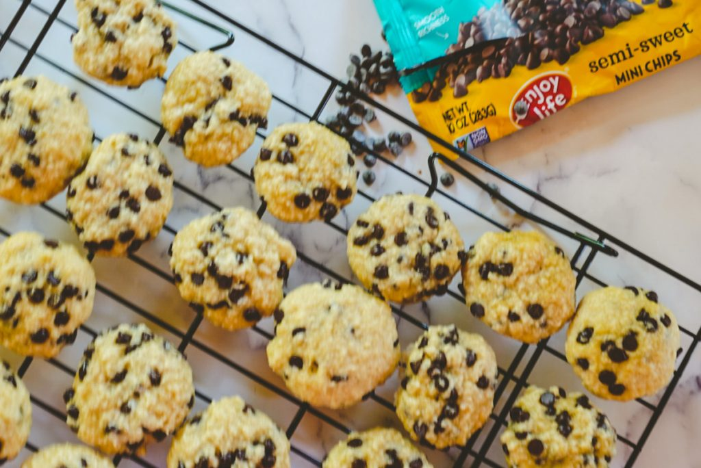 cookies on a cooling tray with chocolate chips in background
