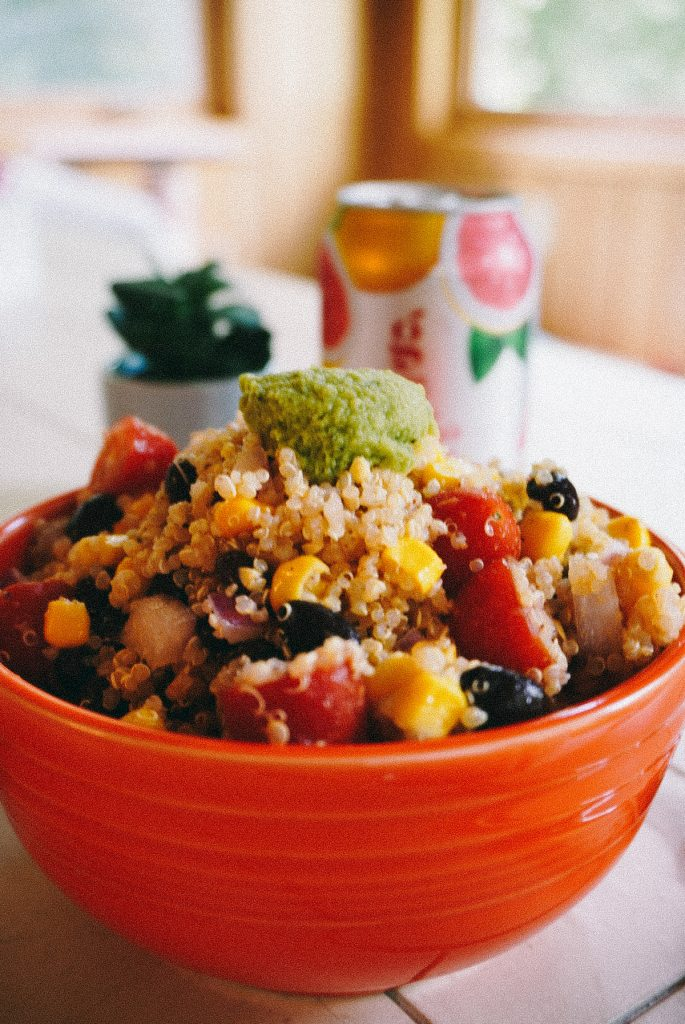 quinoa salad with guacamole in an orange bowl on a table