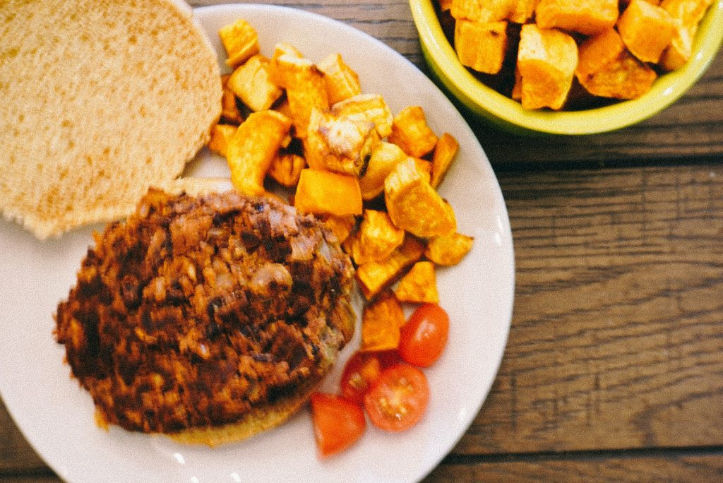 black bean burger on a plate with potatoes