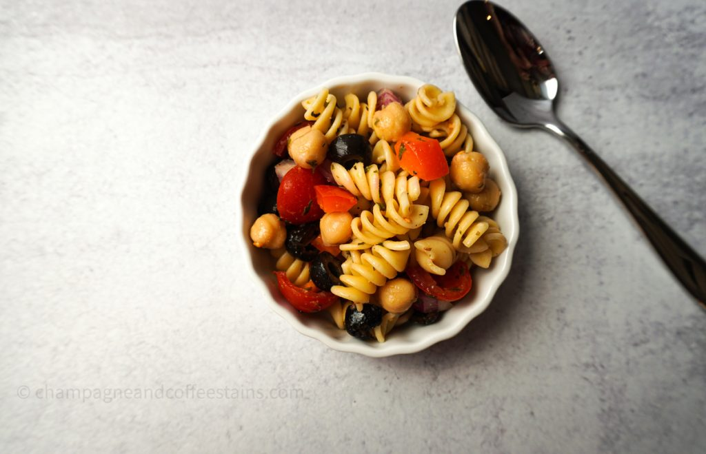 vegan pasta salad in a white bowl with spoon