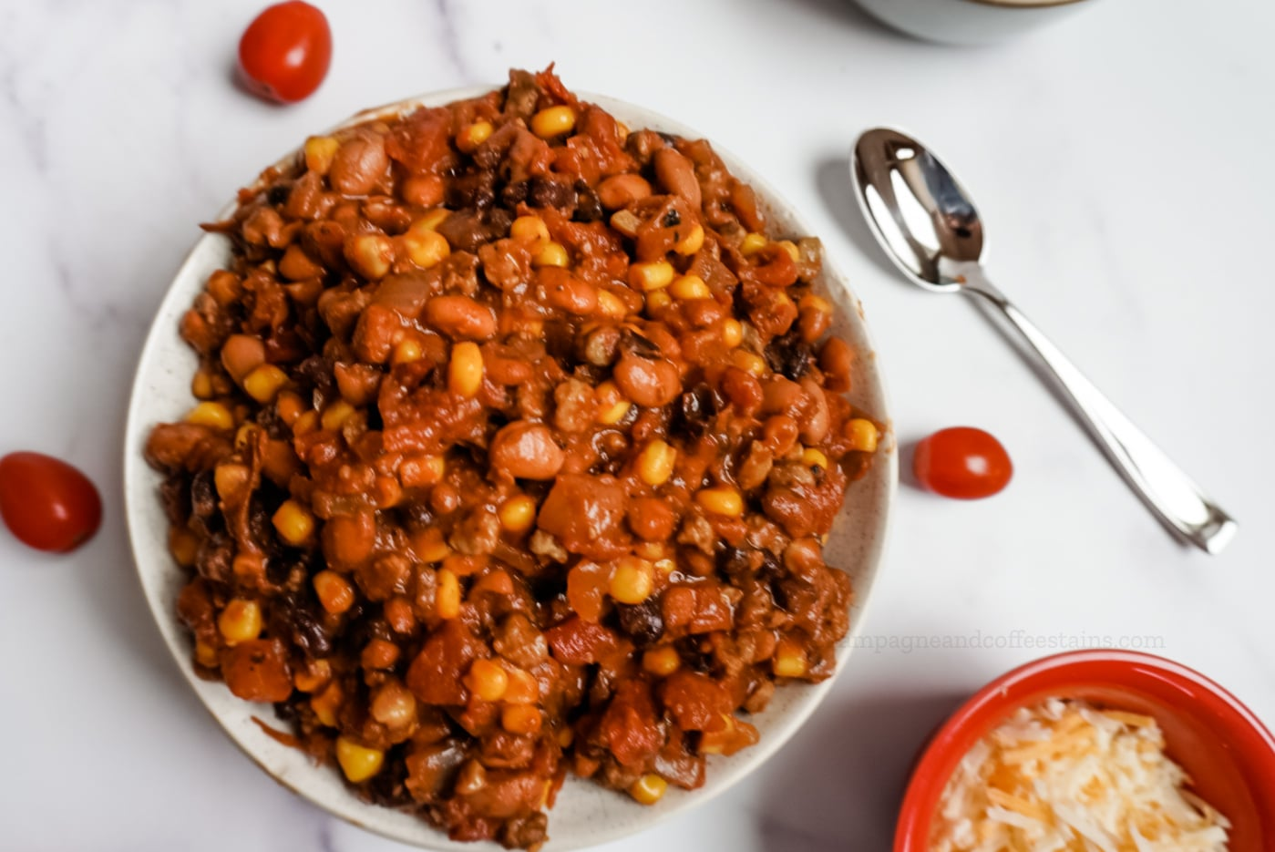 chili in a while bowl with tomatoes and a spoon