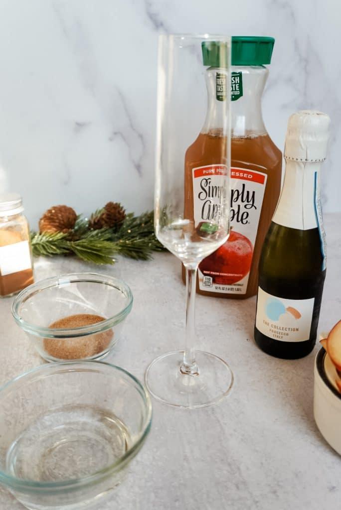 bottle of apple cider, empty champagne flute, bottle of champagne