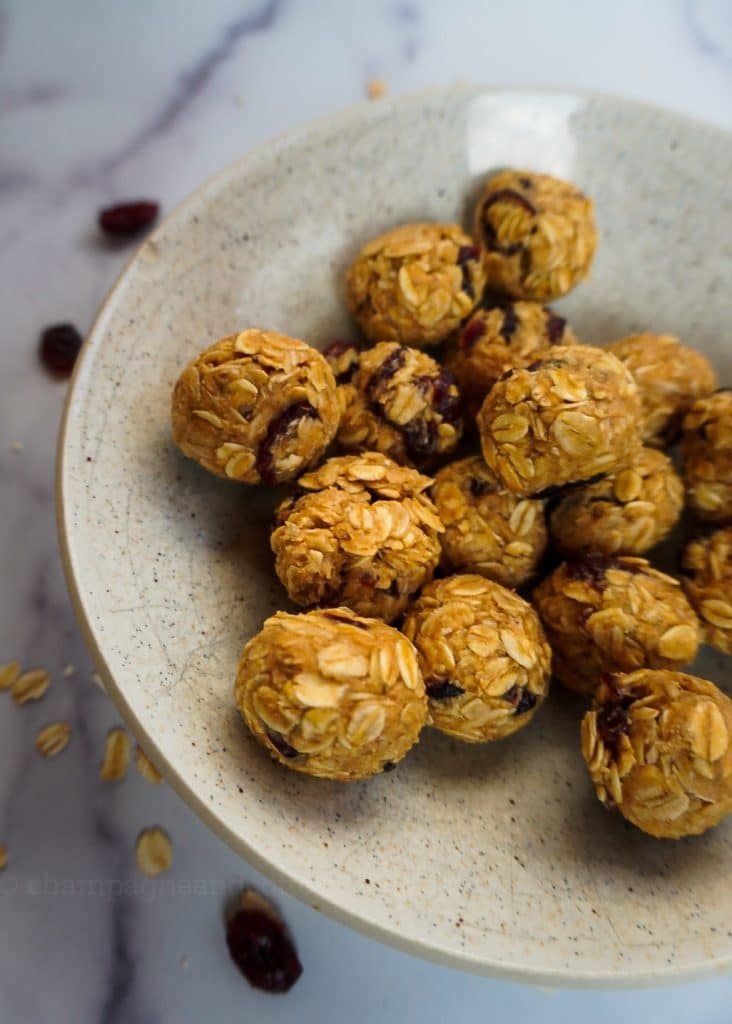 peanut butter and jelly energy balls on a plate with cranberries