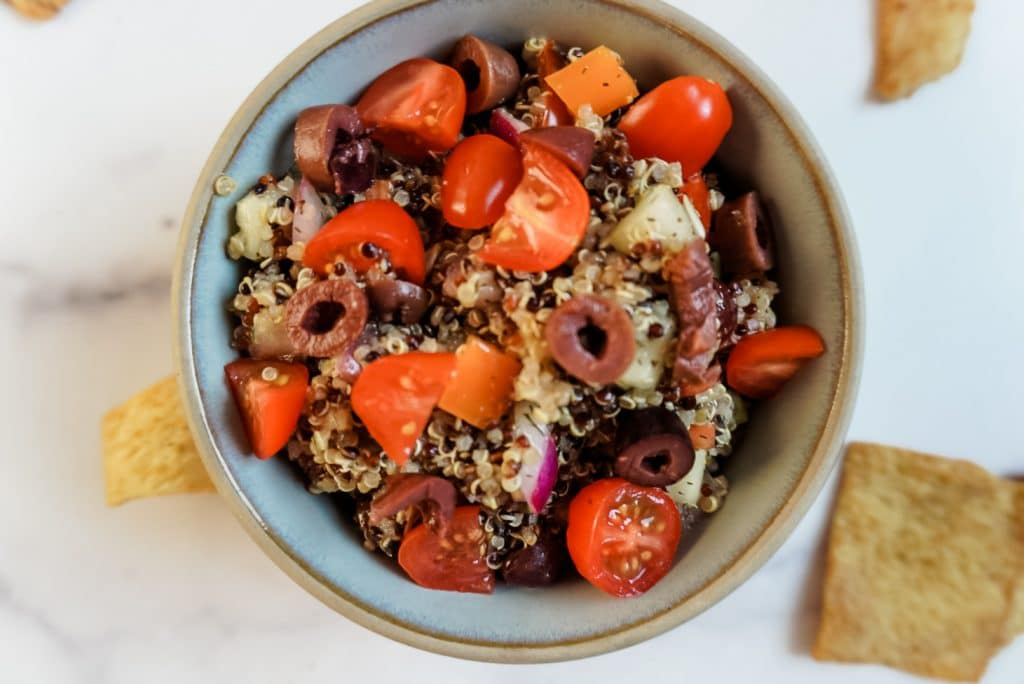 close up of greek quinoa salad in a white bowl