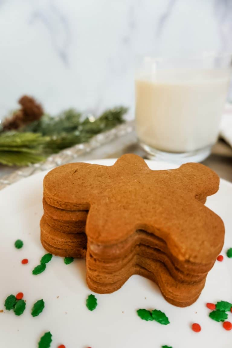 a stack of gingerbread men with milk in the background