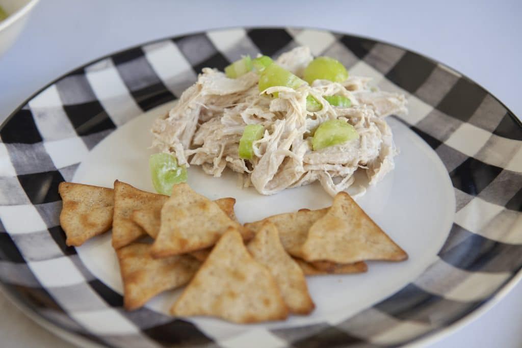 chicken salad in a checkered bowl with pita chips