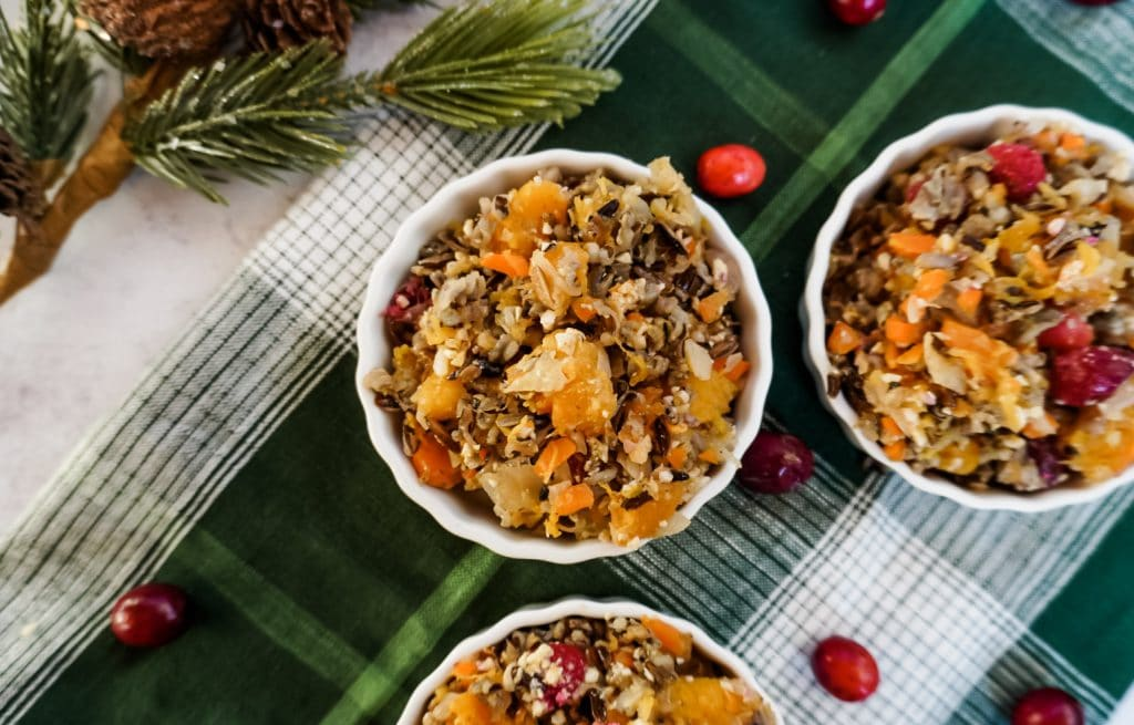 overhead of cranberry squash and wild rice casserole in a white bowl with a green towel