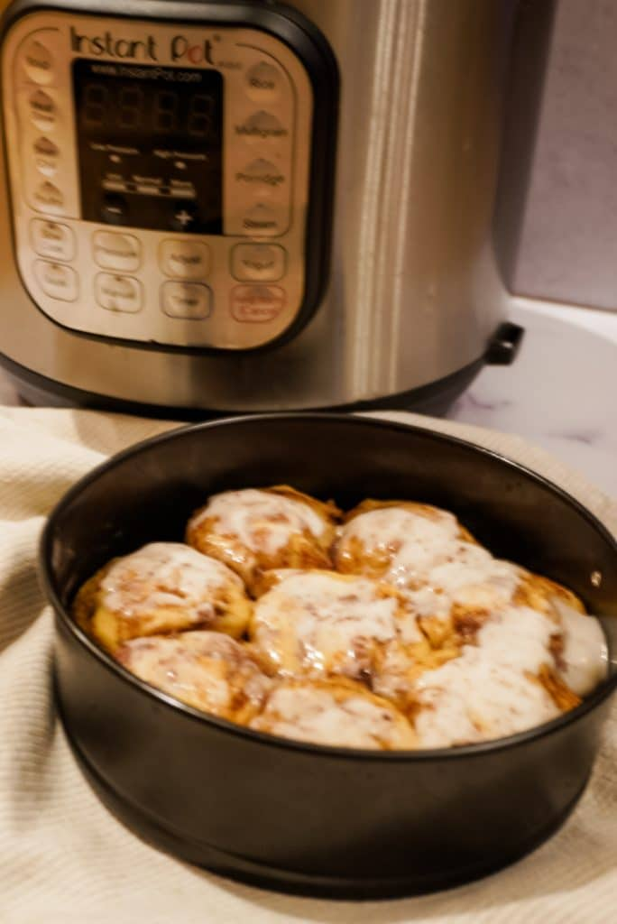 cinnamon rolls in a pan with icing and an instant pot in background