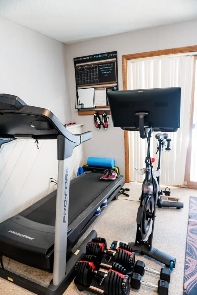 overview of home gym with a treadmill, peloton bike, dumbbells and 1thrive command center