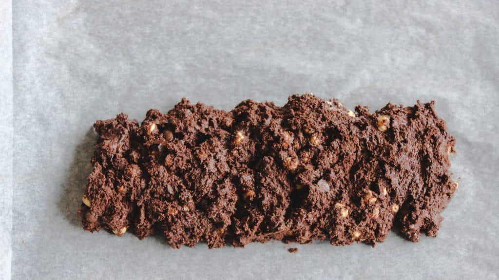 chocolate macadamia biscotti log on parchment paper