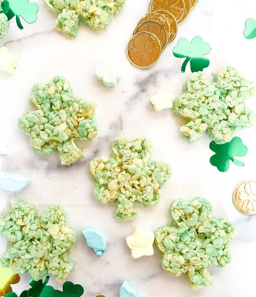 green shamrock rice krispies treats on a white surface with marshmallows and shamrocks