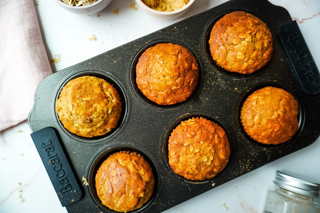 brown sugar maple muffins in a tray with cinnamon on the side
