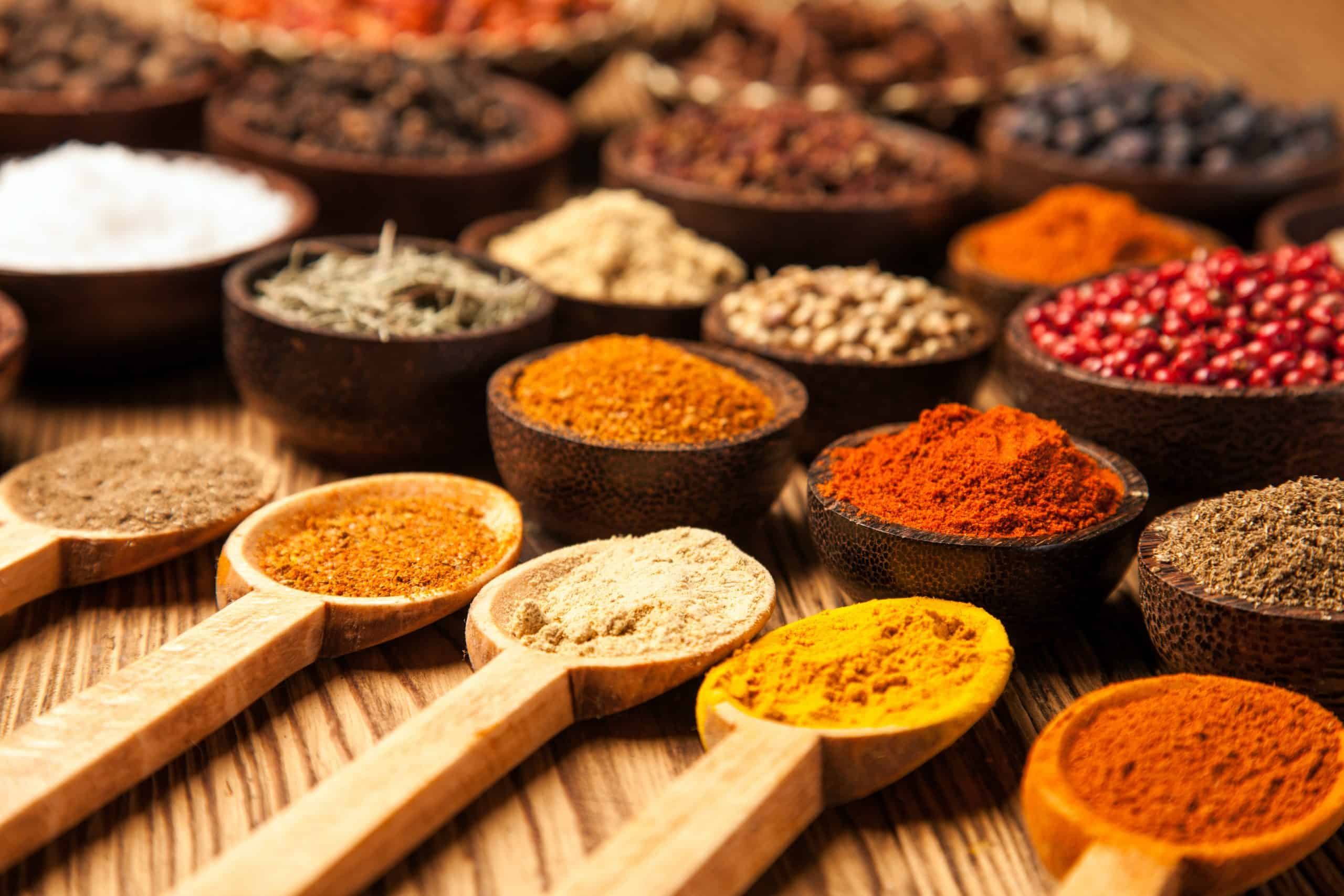Spices and herbs in wooden bowls.